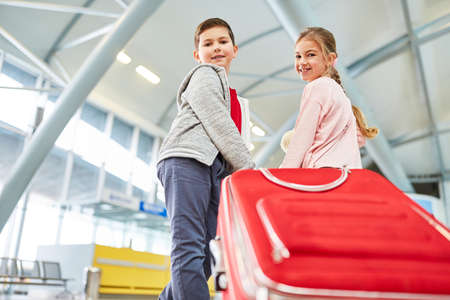 Siblings in the airport terminal with suitcase together make a plane trip during the holidays Archivio Fotografico