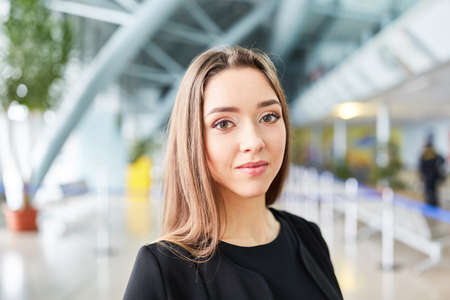 Young woman as a passenger in the airport terminal before departure or at stopover