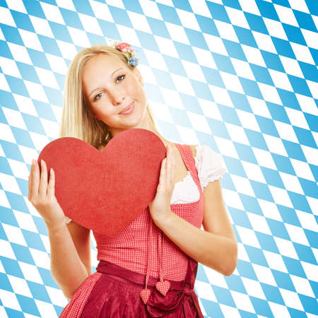 Smiling young woman in a dirndl holds a big red heart