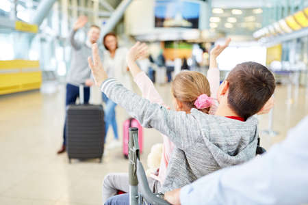 Children waving greetings or goodbyes at the airport or train station Archivio Fotografico