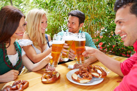 Happy friends in beer garden in traditional Bavarian clothes drinking beer together Standard-Bild