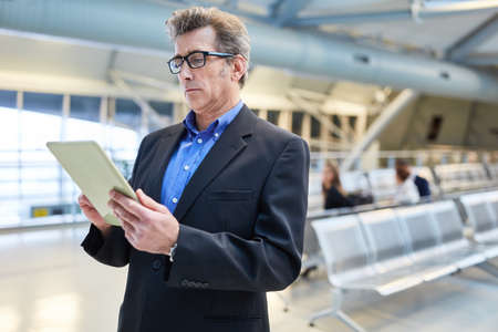 Businessman with tablet PC reads news in airport terminal before his business trip