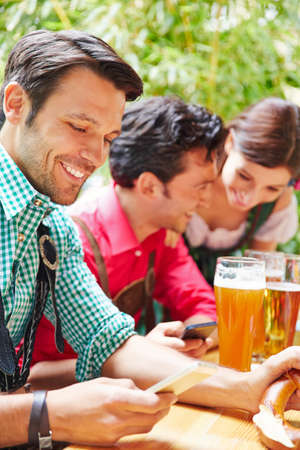 People look at their smartphone in the beer garden in Bavaria