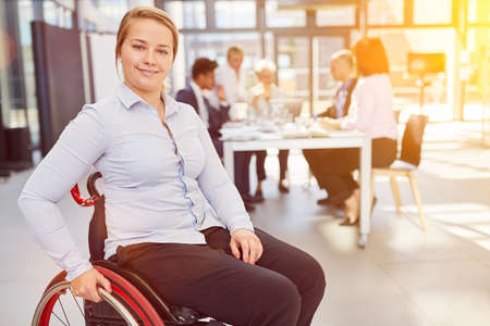 Disabled woman in wheelchair in business office as inclusion concept