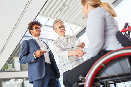 Business people handshaking with colleague in a wheelchair for inclusion and diversity Stock Photo