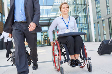 Disabled businesswoman in wheelchair on departure after meeting or congress