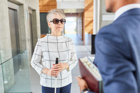 Blind old woman with cane in business office talks to a businessman