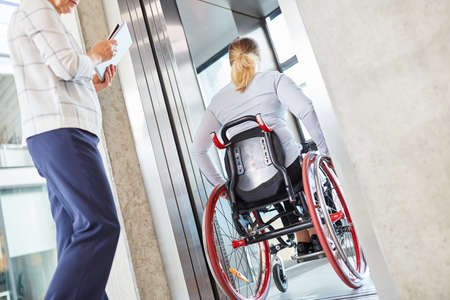 Woman in a wheelchair traveling with the elevator in the business company