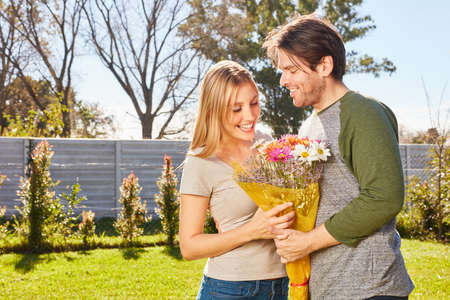 Young woman is glad about flowers of her friend in the summer in the garden