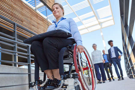 Disabled business woman on ramp in front of the office for inclusion and accessibility Stock Photo