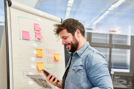 Business man or graphic designer using smartphone in front of a flipchart with organization chart