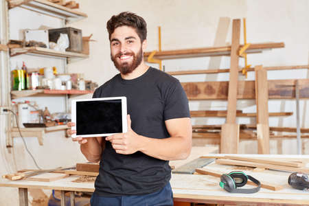 Young man as founder of a craftsman company presents a tablet computer