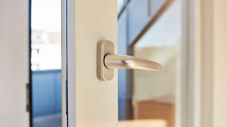 Open door on balcony with door handle on day as intrusion and security concept Фото со стока