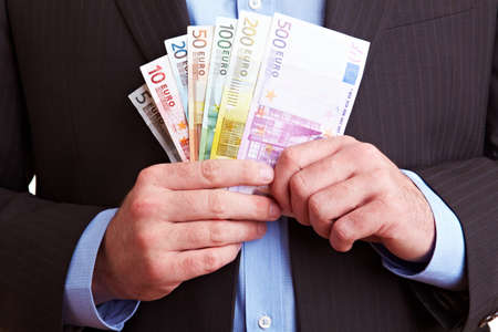 Hands in business suit hold euro banknotes