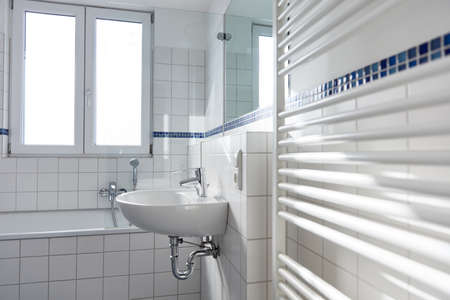 White ceramic sink in bright bathroom with radiator and window 免版税图像