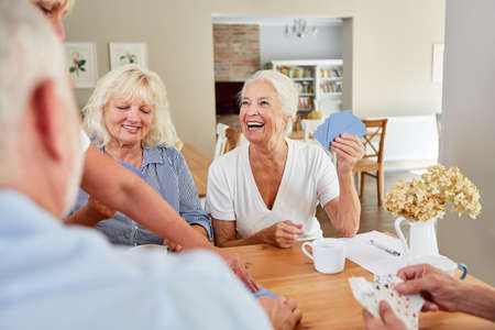Senior woman wins while playing cards with other seniors retired