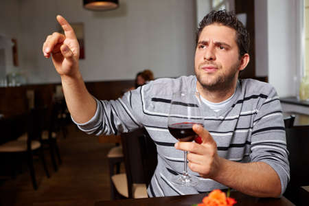 Man in the restaurant complains about a red wine