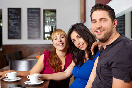 Three friends are laughing in the cafe Stock Photo