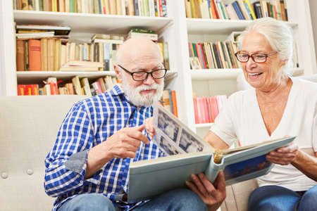 Senior couple with dementia or Alzheimer looks at album photos as a reminder