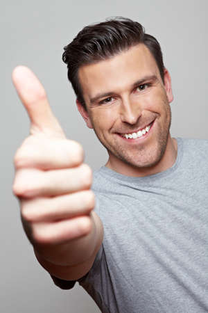 Laughing attractive man holds his thumb up