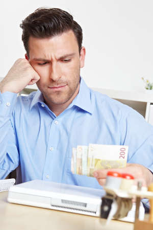 Worried man in the office looks at euro notes