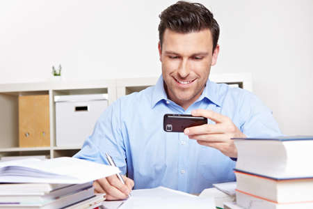 Smiling man looks at smartphone while studying at the desk