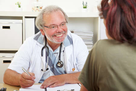Friendly doctor at the desk in his practice advises an elderly patient