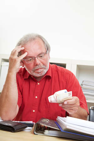 Concerned pensioner looks thoughtfully at euro banknotes in his hand