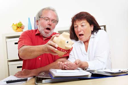 Shocked seniors shake an empty piggy bank at a desk