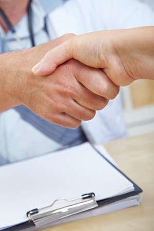 Handshake at the doctor over a desk with a clipboard Reklamní fotografie