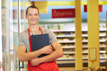 Smiling seller with clipboard leans against refrigerated shelf in supermarket