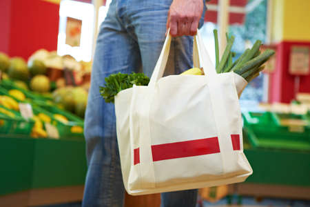 Man carries full shopping bag with fruits and vegetables