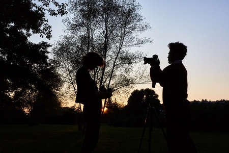Two photographers as nature photographers with cameras at dusk Stok Fotoğraf