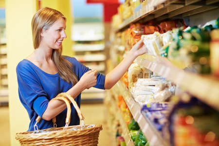 Woman stands in supermarket with shopping basket on shelf for pasta