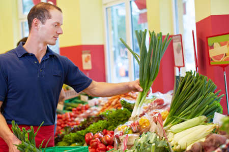 Smiling supermarket trainee fills up leek at the vegetable stall