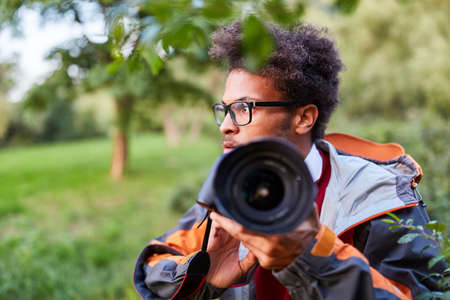 Young man as paparazzo photographer or detective with camera in nature