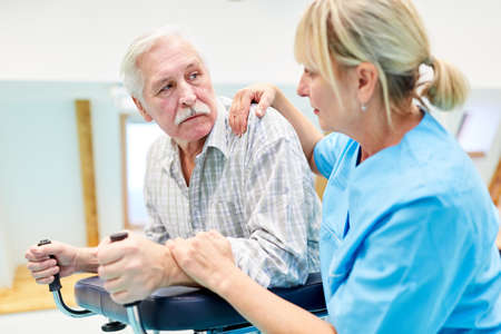 Depressed senior patient with walker in physiotherapy gets comfort