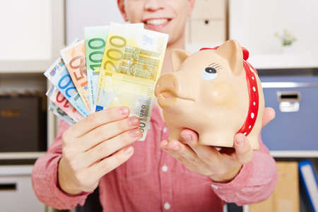 Hands of a laughing man hold euro notes and piggy bank