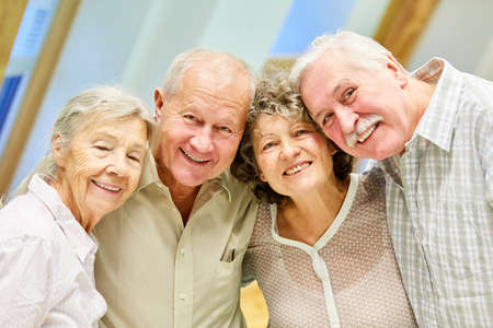 Four senior citizens as pensioners smile happily at home or in a retirement home
