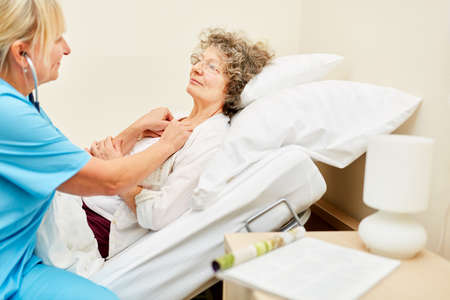A bedridden old woman is being listened to by a doctor with a stethoscope