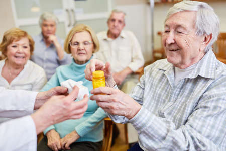 Senior as a patient in a health course with pills and tablet dispenser