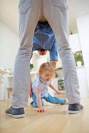 Father lifts daughter off the floor in the kitchen after an accident