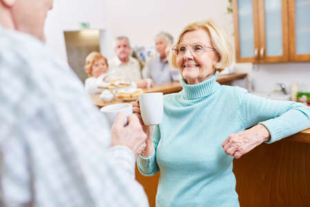 Smiling retiree drinks a cup of coffee while talking small at a senior meeting