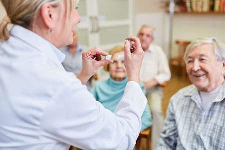 Doctor in seminar on health counseling explains seniors a dosing inhaler