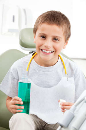 Laughing child with mouthwash sits at the dentist Stock fotó