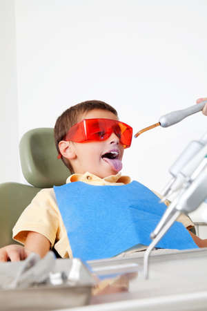 Child with protective glasses at the dentist sticks out his tongue Stock fotó