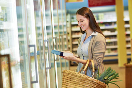 Young woman with shopping basket takes frozen foods from refrigerated shelves in supermarket Reklamní fotografie