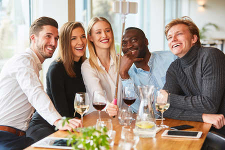 Young people take a selfie photo with the selfie stick in the restaurant or pub