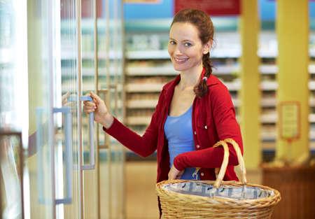 Elderly smiling woman is standing in the supermarket at the cooling shelf Reklamní fotografie