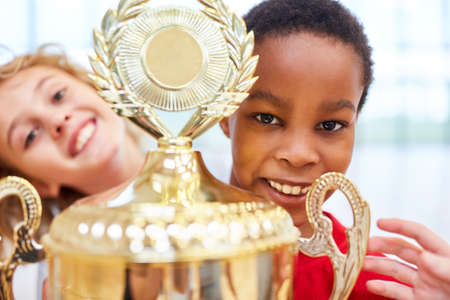 African boy holds the winner cup after a competition in school sport